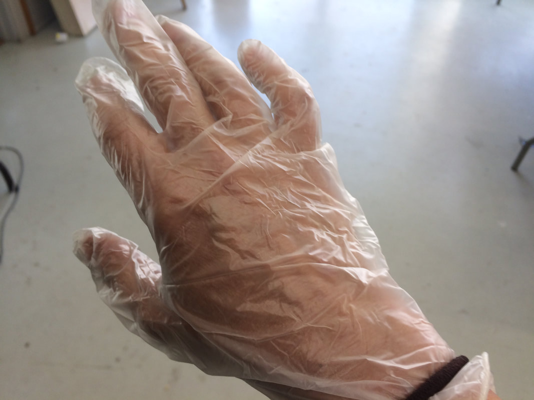 Image Description: The back of a right hand wearing a clear vinyl glove, held in place with a thick hair elastic around the wrist.